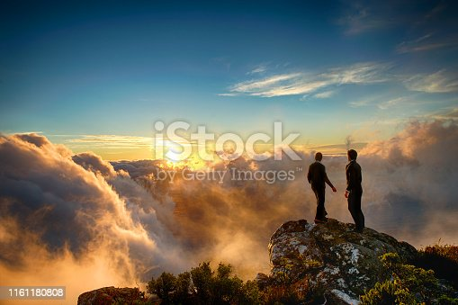 Caucasian Male and Mixed Race Female Businessman and Businesswoman together on top of a mountain at a spectacular sunset shaking hands and looking out Cape Town South Africa