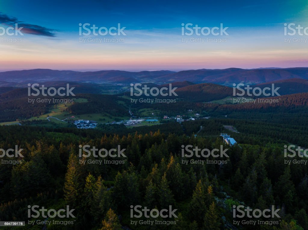 Sunset. Aerial view of the summer time in mountains near Czarna Gora mountain in Poland. Pine tree forest and clouds over blue sky. View from above. stock photo