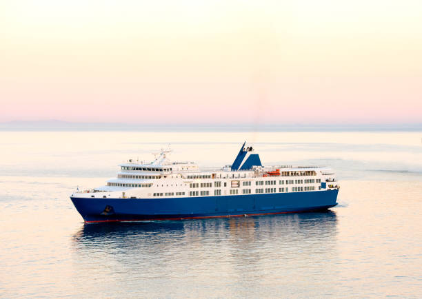 Sunset and a blue white ferry boat in greek islands stock photo