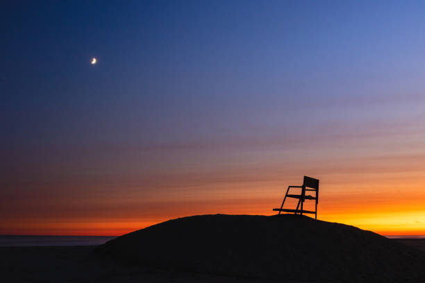 Sunset and crescent moon over a beach, with a lifeguard tower silhouetted. Long Beach New York