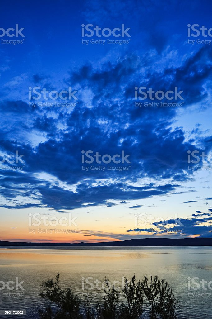 Sunset and dark cloud in the fjord in Novigrad stock photo