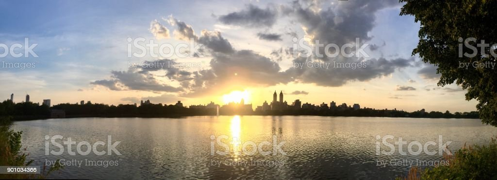 Sunset and silhouette buildings reflects on water at Jacqueline Kennedy Onassis reservoir in panorama stock photo