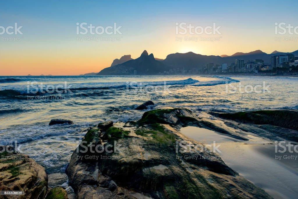 Sunset and stones at Ipanema beach stock photo