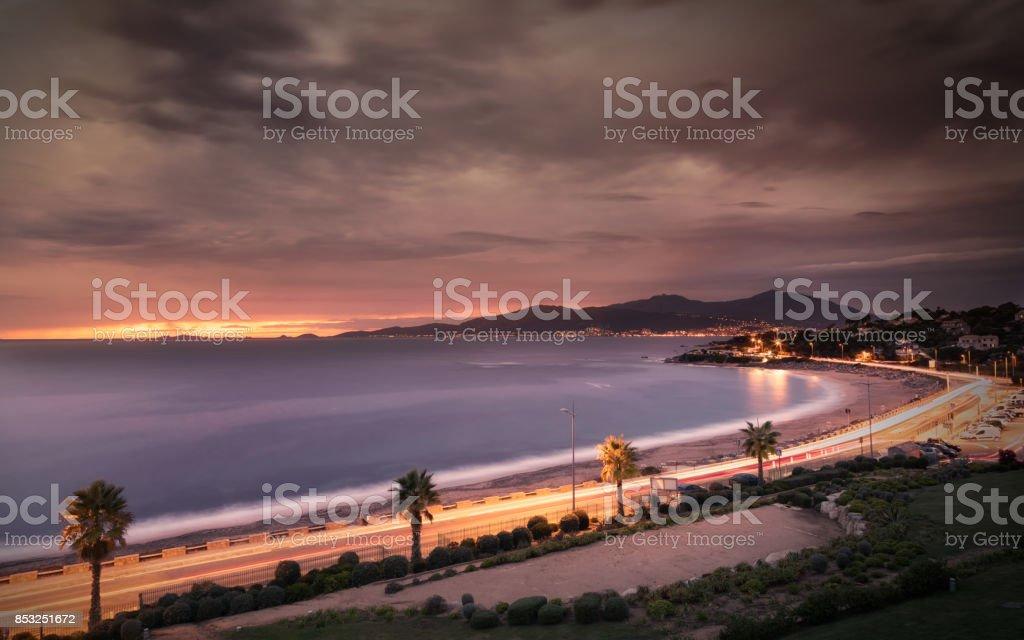 Puesta de sol y nubes tormentosas sobre playa de Porticcio Córcega - foto de stock