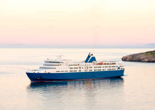 Sunset and the blue white ferry boat in greek islands stock photo