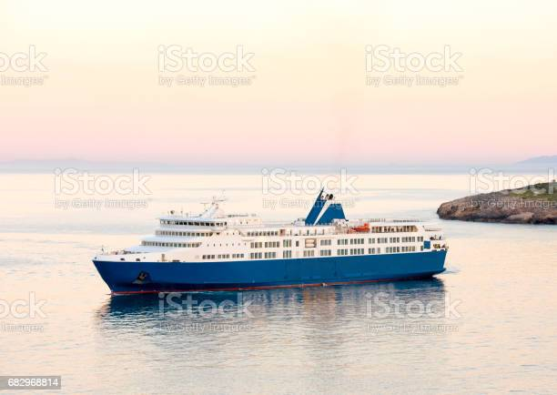 Sunset and the blue white ferry boat in greek islands