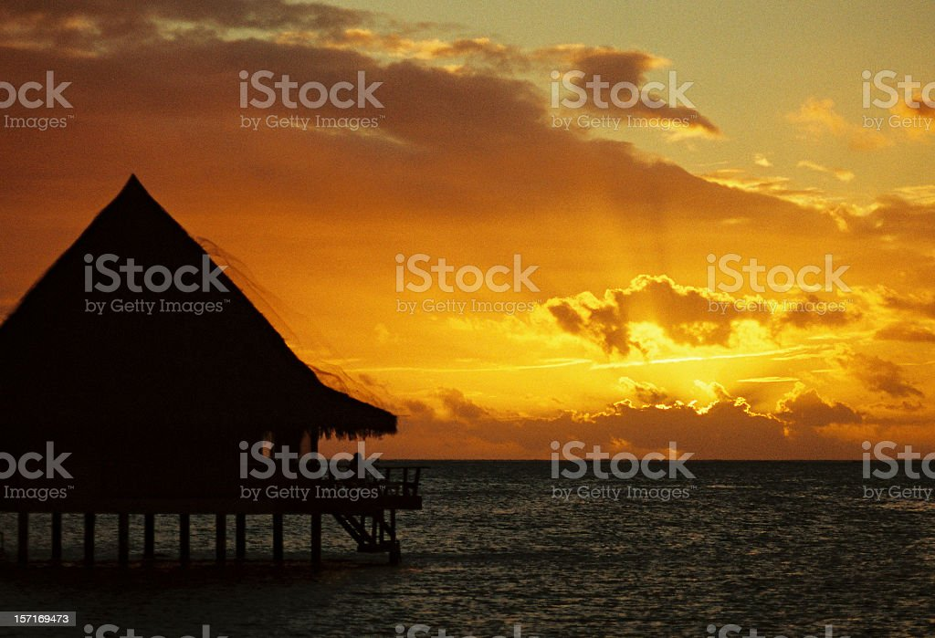 Sunset and tropical bungalow stock photo