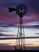 Beautiful sunset over the western Kansas prairie with windmill silouette in foreground
