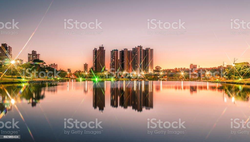 Pôr do sol em um lago de um parque com a cidade no fundo - foto de acervo