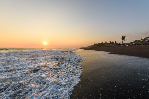 istock Sunset at Beach with Black Sand in Monterrico, Guatemala. Known for its volcanic black sand beaches and annual influx of sea turtles. Travel destination of Guatemala. Monterrico is situated on the Pacific coast in the department of Santa Rosa. 917225010
