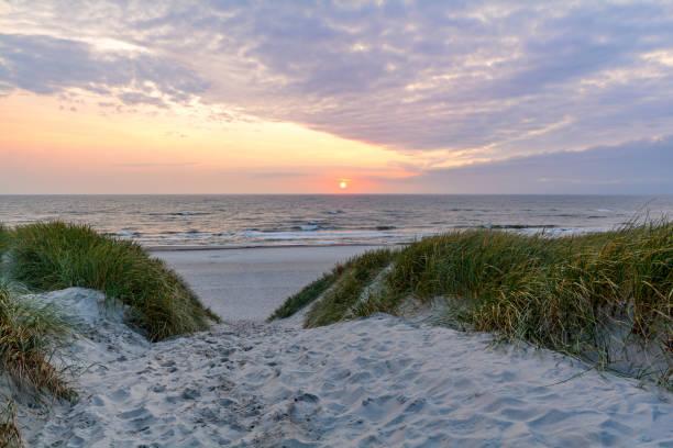 Pôr do sol na praia com paisagem de dunas de areia perto de Henne Strand, Jutland Dinamarca - foto de acervo