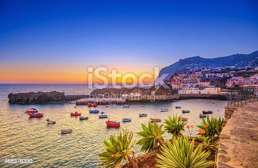 The beautiful fishing village of Camara de Lobos on the portugese Island of Madeira at sunset; in the back the landmark Cabo Girao, the world second highest steep cliff (580 m).