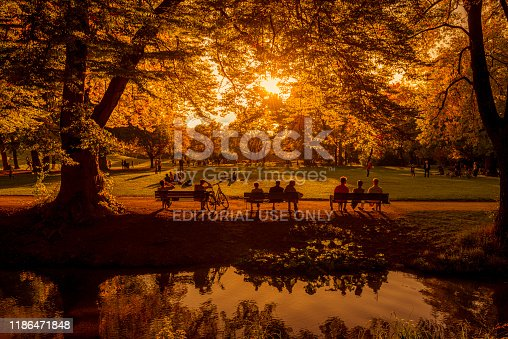 Munich, Germany October 13, 2019: Sunset at english garden in Munich. People resting under the trees.