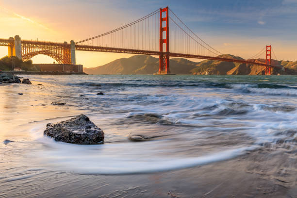Sunset at Golden Gate Bridge Long exposure of a stunning sunset at the beach by the famous Golden Gate Bridge in San Francisco, California golden gate bridge stock pictures, royalty-free photos & images
