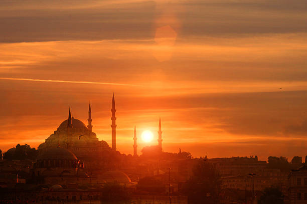 sunset at istanbul, with sun behind silhouette of blue mosque - ramadan stock photos and pictures
