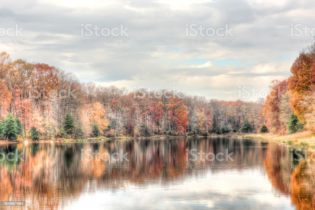Sunset at Lake Woodglen in Fairfax, Virginia near residential neighborhood, with orange foliage autumn trees forest, water reflection, houses, rocky beach shore stock photo
