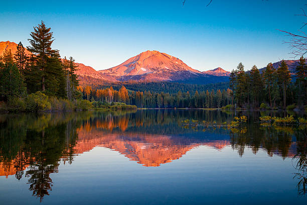 Sunset at Lassen Peak with reflection on Manzanita Lake Sunset at Lassen Peak with reflection on Manzanita Lake, Lassen Volcanic National Park, California volcanic landscape stock pictures, royalty-free photos & images