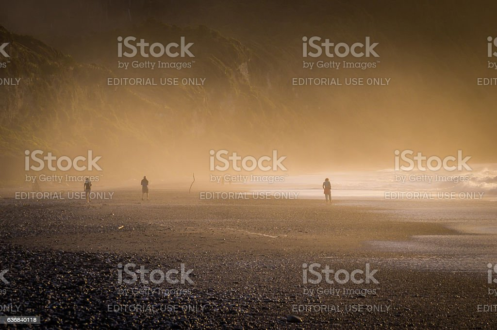 Sunset at misty pebble beach in New Zealand stock photo