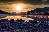 istock Sunset at Rotevatnet in Volda, Norway with citylights in background and stones in forefront 1325577545