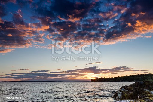Sunset at Sand Beach, Mount Desert Island, Maine, USA. Dramatic sky with sunburst as the sun sets on the horizon.