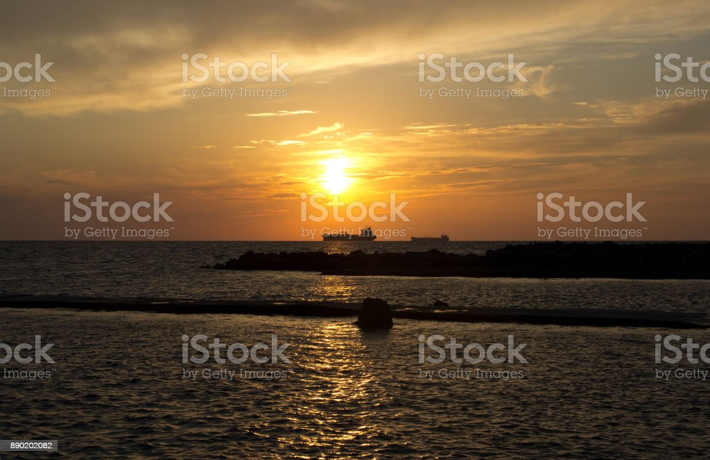 Sunset at sea and the silhouettes of two ships stock photo