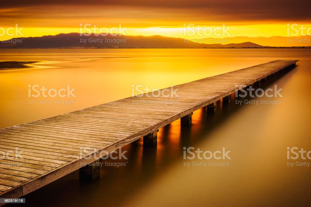 sunset at sea in front of wood pier in El trabucador, Delta del Ebro. Spain - Royalty-free Atmospheric Mood Stock Photo