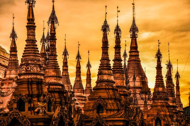 sonnenuntergang im shwedagon paya im rangun, myanmar - aurum stock-fotos und bilder