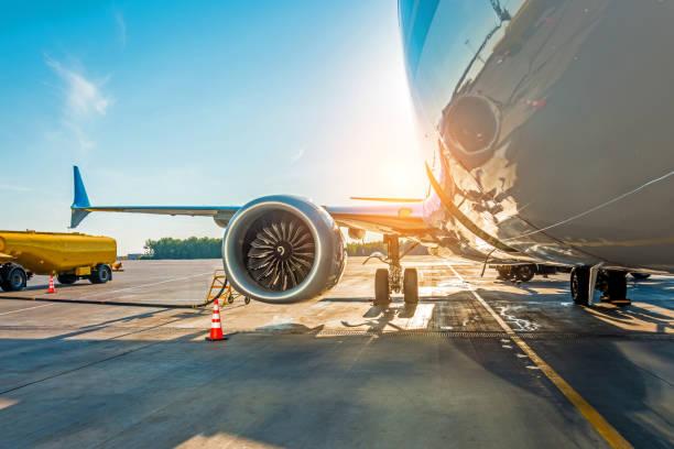 sonnenuntergang am flughafen. tanken das flugzeug vor dem flug, flugkraftstoff wartung am flughafen. - benzintank stock-fotos und bilder