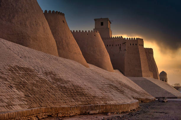 zonsondergang bij de oude stadsmuren van khiva, silk road, oezbekistan - karavanserai stockfoto's en -beelden