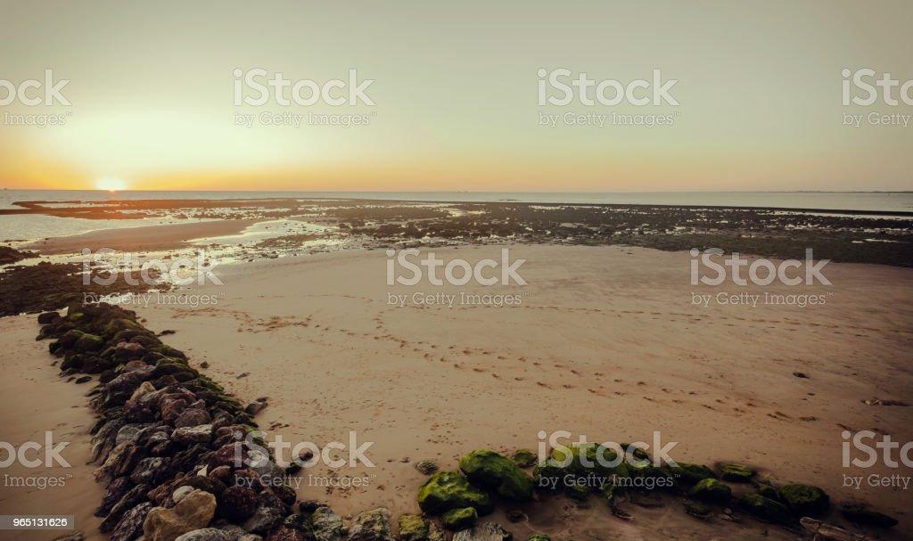 Sunset at the beach of Sanlúcar de Barrameda at low tide and orange sky zbiór zdjęć royalty-free