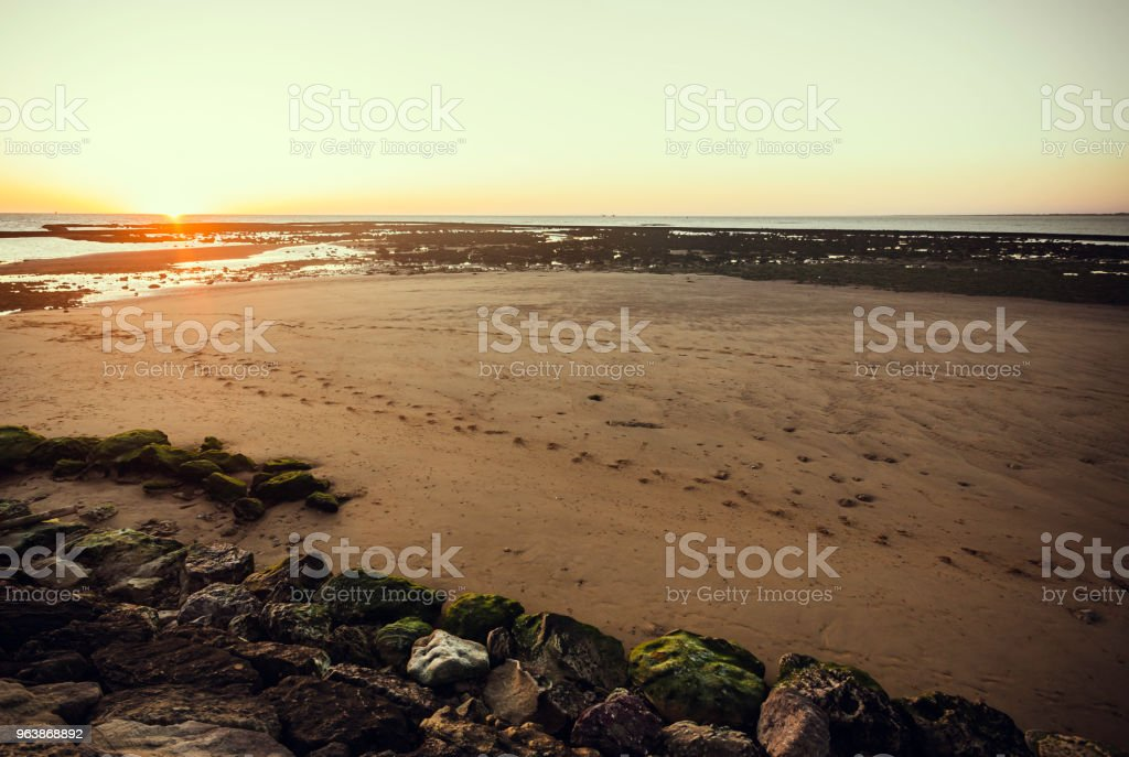 Sunset at the beach of Sanlucar de Barrameda with low tide and reddish sky - Royalty-free Backgrounds Stock Photo