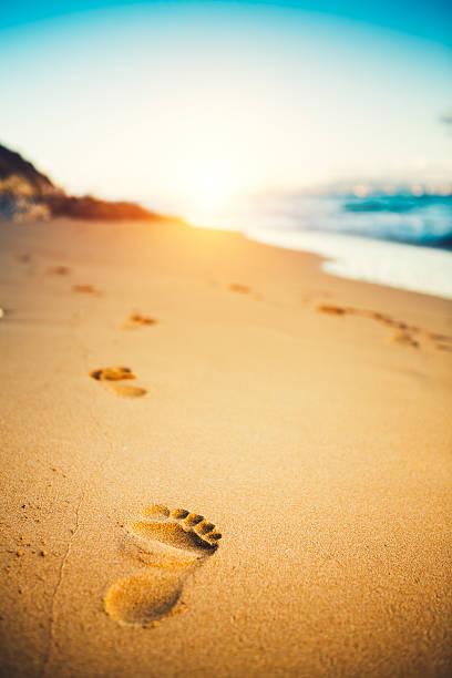 sonnenuntergang am strand mit fußspuren im sand - fußspuren stock-fotos und bilder