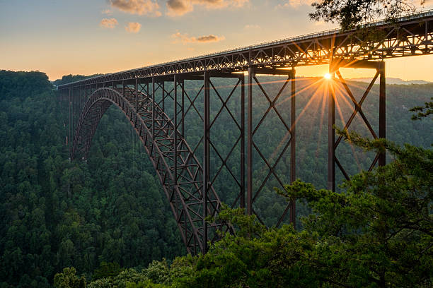 Sunset at the New River Gorge Bridge in West Virginia Setting sun behind the girders of the high arched New River Gorge bridge in West Virginia appalachia stock pictures, royalty-free photos & images