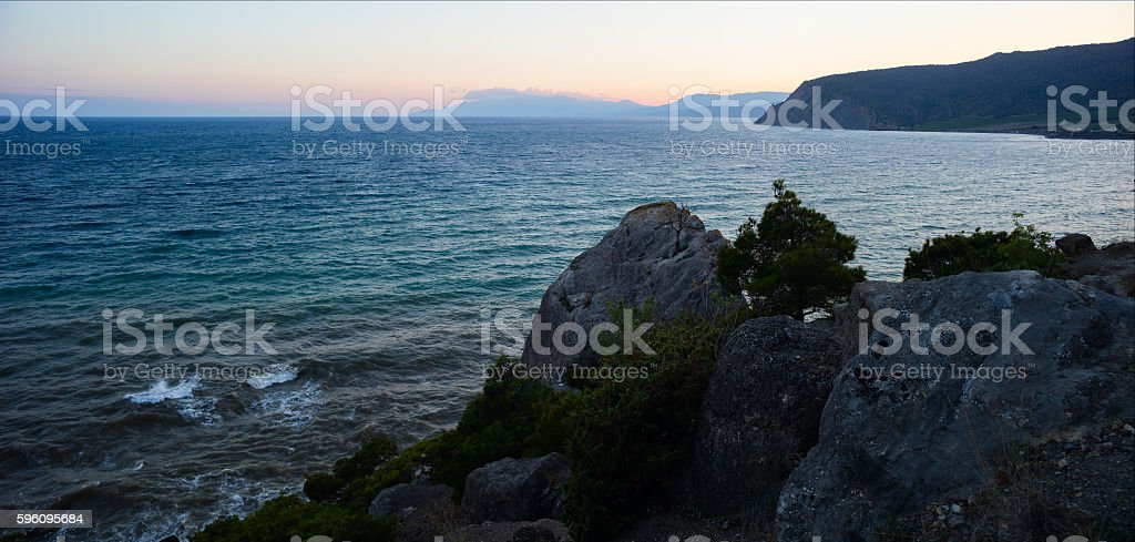 Sunset at the sea shore of a beach with rocks royalty-free stock photo