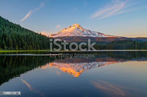 Trillium Lake in Oregon at the water's edge of the lake to see golden light on Mount Hood peak during sunset. Mount Hood mountain had golden light shining on the peak at sunset. A beautiful sunset adventure at Trillium lake near Portland, Oregon in the Pacific Northwest after a hike. Reflections of Mt Hood were seen in Trillium Lake water with trees around the lake. There were amazing clouds in the sky during sunset at Trillium lake with a view of Mount Hood.