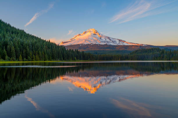 Sunset at Trillium Lake and Mount Hood reflections Trillium Lake in Oregon at the water's edge of the lake to see golden light on Mount Hood peak during sunset. Mount Hood mountain had golden light shining on the peak at sunset. A beautiful sunset adventure at Trillium lake near Portland, Oregon in the Pacific Northwest after a hike. Reflections of Mt Hood were seen in Trillium Lake water with trees around the lake. There were amazing clouds in the sky during sunset at Trillium lake with a view of Mount Hood. mt hood stock pictures, royalty-free photos & images