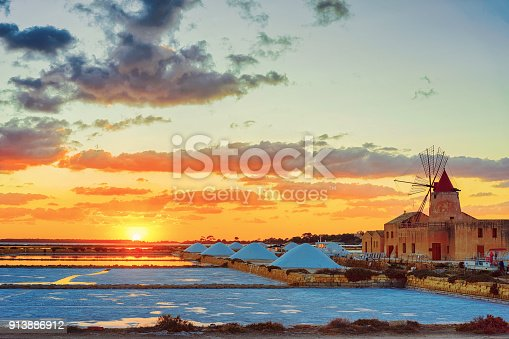 Sunset at Windmill in the salt evoporation pond in Marsala, Sicily island, Italy