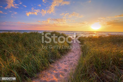 Sandy beach trail winds through dune grass to a sunset horizon on the shores of Lake Michigan in Hofffmaster State Park.