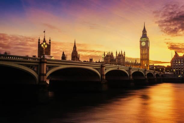 zonsondergang balken over de klokkentoren van de big ben in londen, verenigd koninkrijk. - londen engeland stockfoto's en -beelden