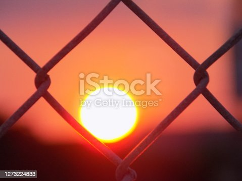 Off-centered sunset from behind chainlink fence in Corpus Christi, Texas USA in September 2020.