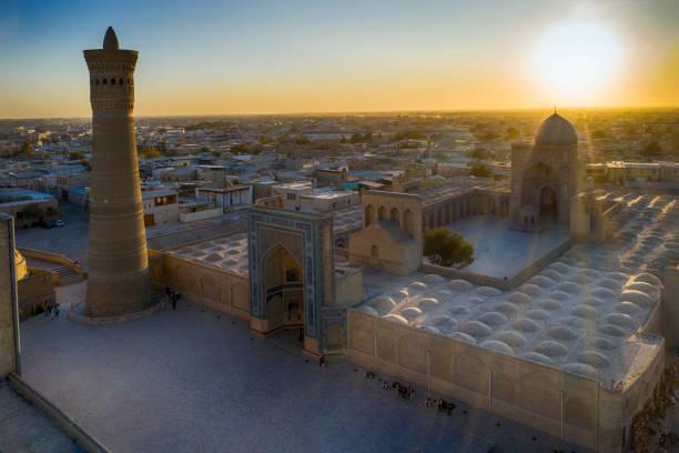 zonsondergang achter kaylan minaret, bukhara, historische zijderoute, oezbekistan - karavanserai stockfoto's en -beelden