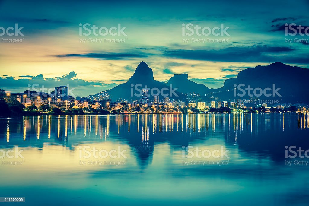 Sunset behind mountains in Rio de Janeiro with water reflection stock photo