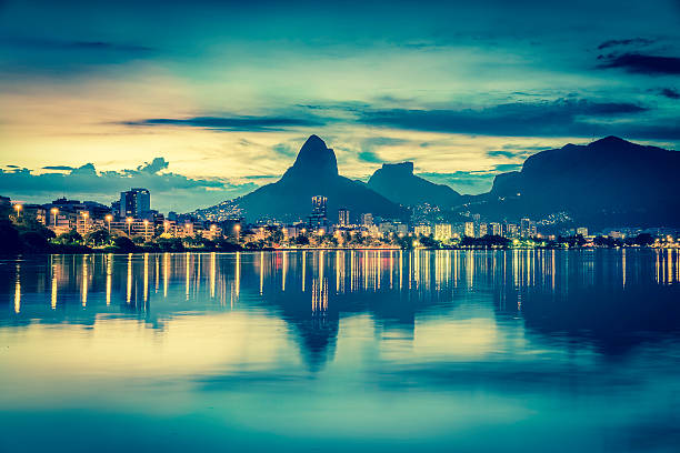Sunset behind mountains in Rio de Janeiro with water reflection Sunset behind mountains in Rio de Janeiro with water reflection, Brazil lagoa rio de janeiro stock pictures, royalty-free photos & images