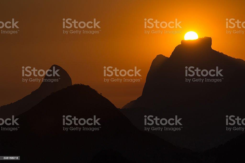 Sunset behind mountains stock photo
