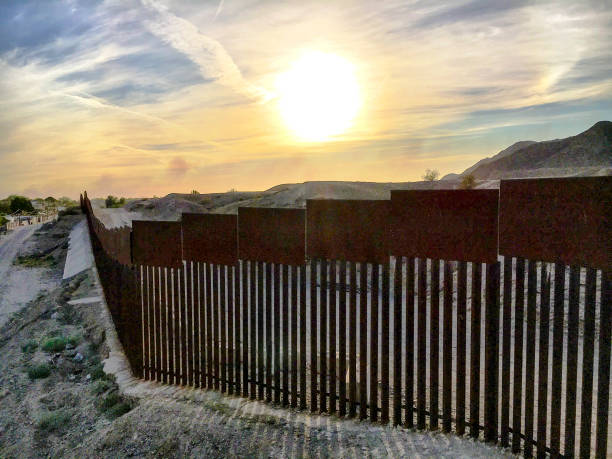 Sunset behind the border The international border fence between the US and Mexico at Los Algodones,  international border barrier stock pictures, royalty-free photos & images