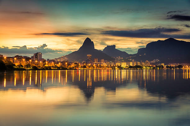 Sunset behind the mountains in Rio de Janeiro, Brazil Sunset behind mountains in Rio de Janeiro with water reflection, Brazil lagoa rio de janeiro stock pictures, royalty-free photos & images