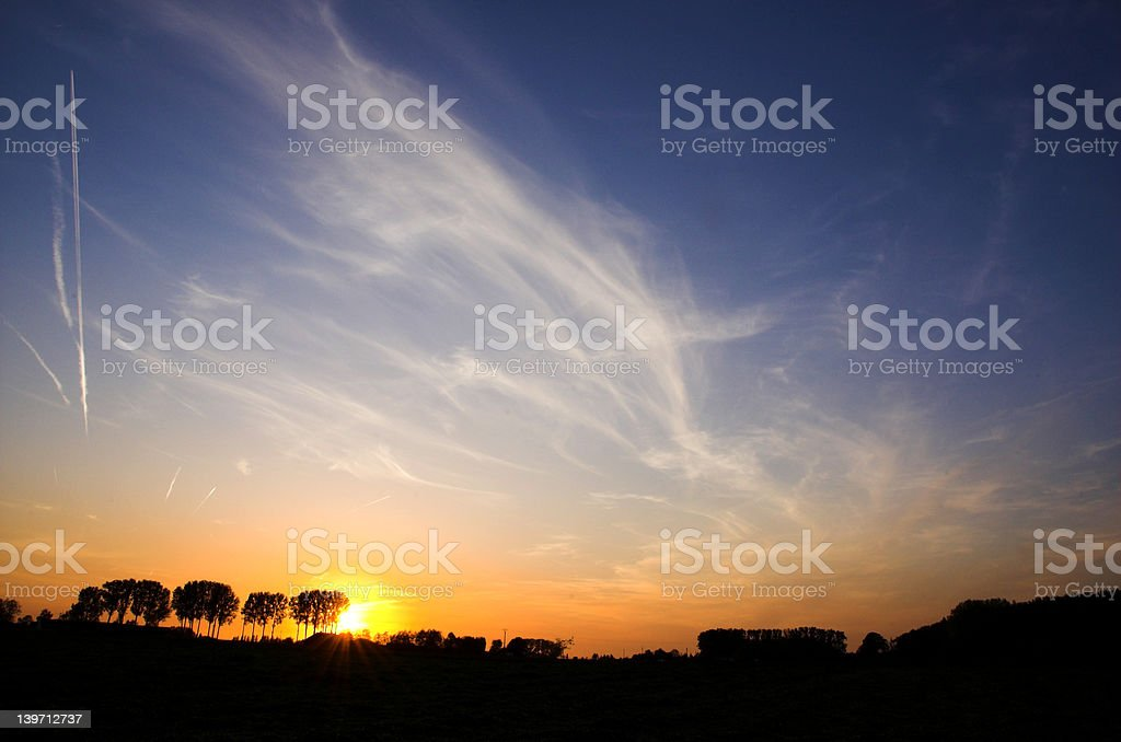 sunset behind trees royalty-free stock photo