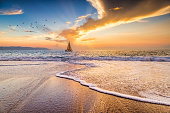 A Sailboat is Sailing Along the Ocean as Birds Fly Above and the Sun Sets on the Ocean Horizon