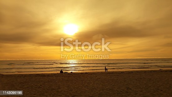 sunset on California beach with people together in silhouette at water's edge