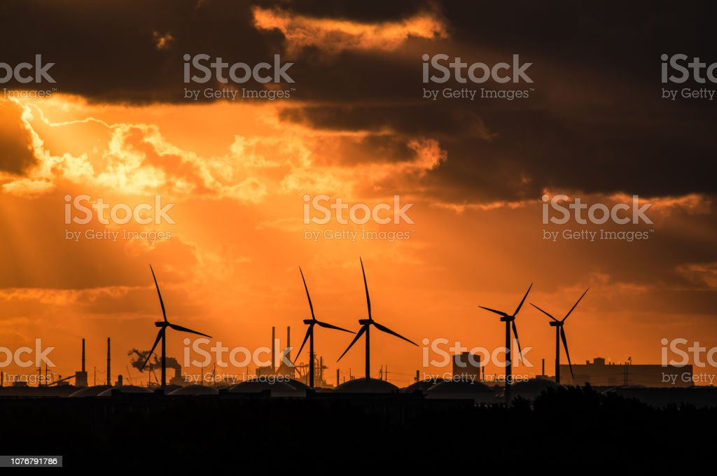 Sunset casting rays through a dramatic orange cloudy sky, onto backlit electric windmills stock photo